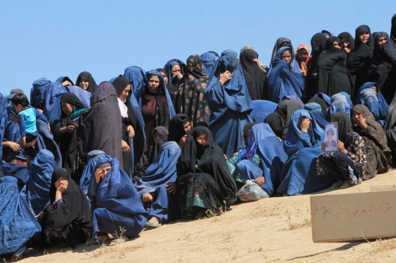 Female villagers attend the burial ceremony of civilians killed by fighters at Mirza Olang village [Reuters]