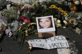 Flowers and a photo of car-ramming victim Heather Heyer lie at a makeshift memorial in Charlottesville, Virginia [Justin Ide/Reuters]