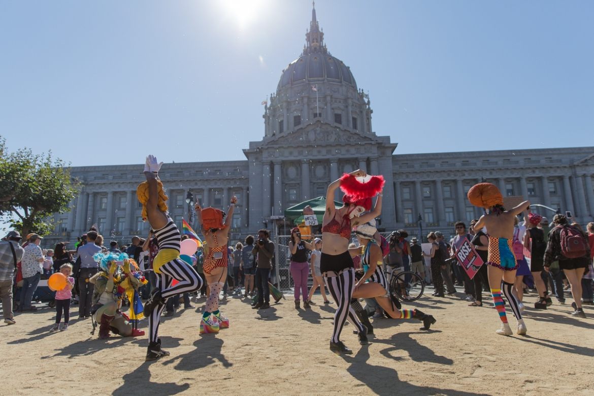 'There's no reason for us to stay inside when there's love to be shared,' says 27-year-old Courtney Russel (centre). She performed with the burlesque clown troupe, Fou Fou Ha, in front of City Hall in San Francisco during a gathering to end the day. [Kelly Lynn Lunde/Al Jazeera]