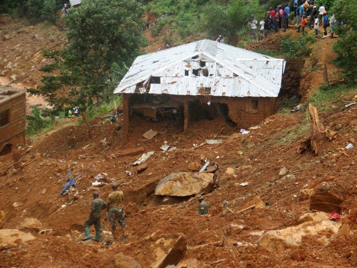 Security forces search for bodies from the scene of heavy flooding and mudslides in Regent, just outside of Sierra Leone's capital Freetown. [Manika Kamara/AP Photo]