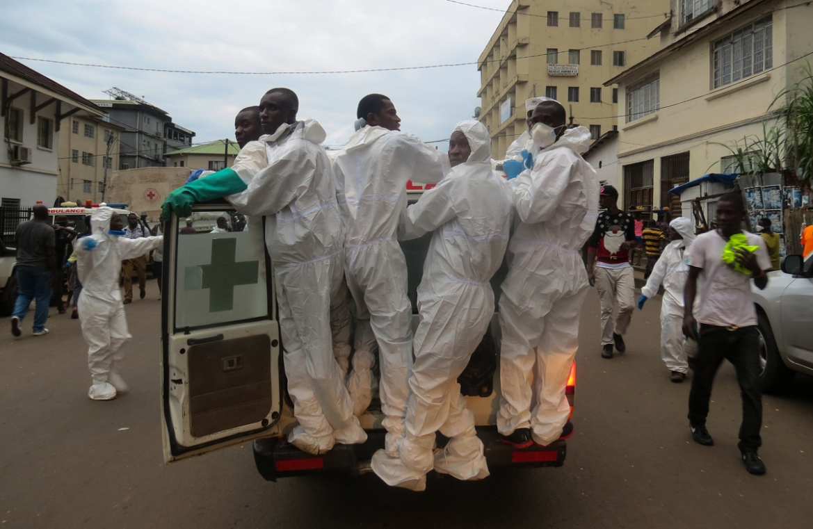 Members of a burial team ride on an ambulance as they leave the Connaught Hospital morgue in Freetown. Sierra Leone is one of the poorest countries in the world and the government has promised relief to more than 2,000 people left homeless. [Saidu Bah/AFP/Getty Images]