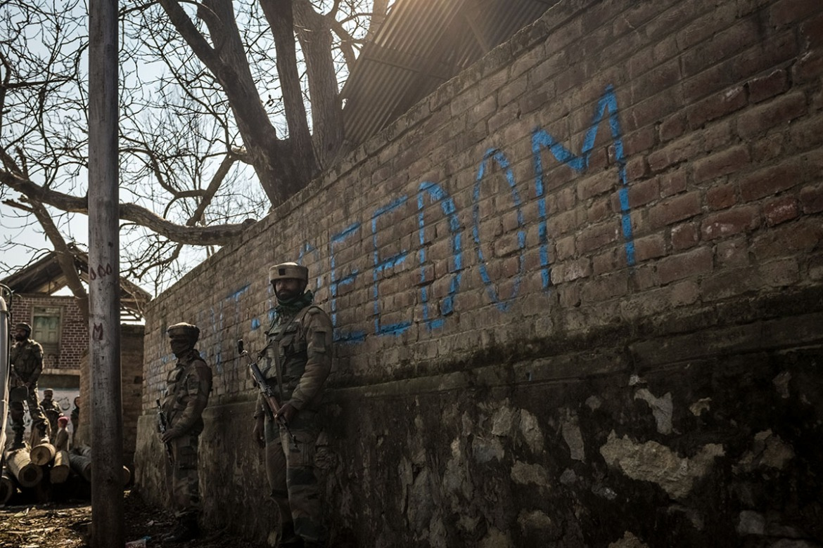 A soldier of the Indian army stands next to a wall with graffiti reading 'Freedom' in the village of Panjpora, located south of Srinagar. [Violeta Santos Moura/Al Jazeera]