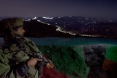 Indian soldier looks at the illuminated fence of the Line of Control between the Indian and Pakistani controlled parts of Kashmir [Getty]