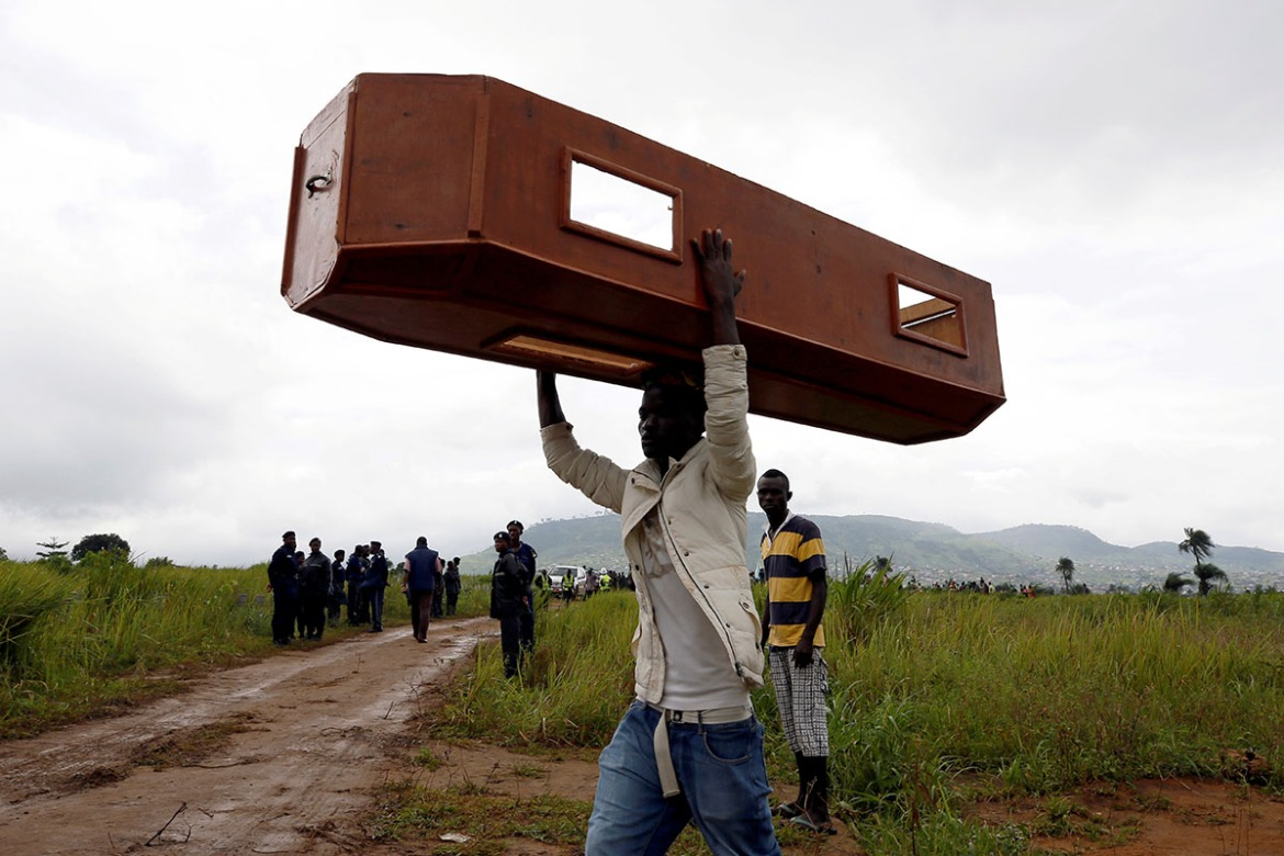 A man carries an empty coffin at the Paloko cemetery in Waterloo. [Afolabi Sotunde/Reuters]