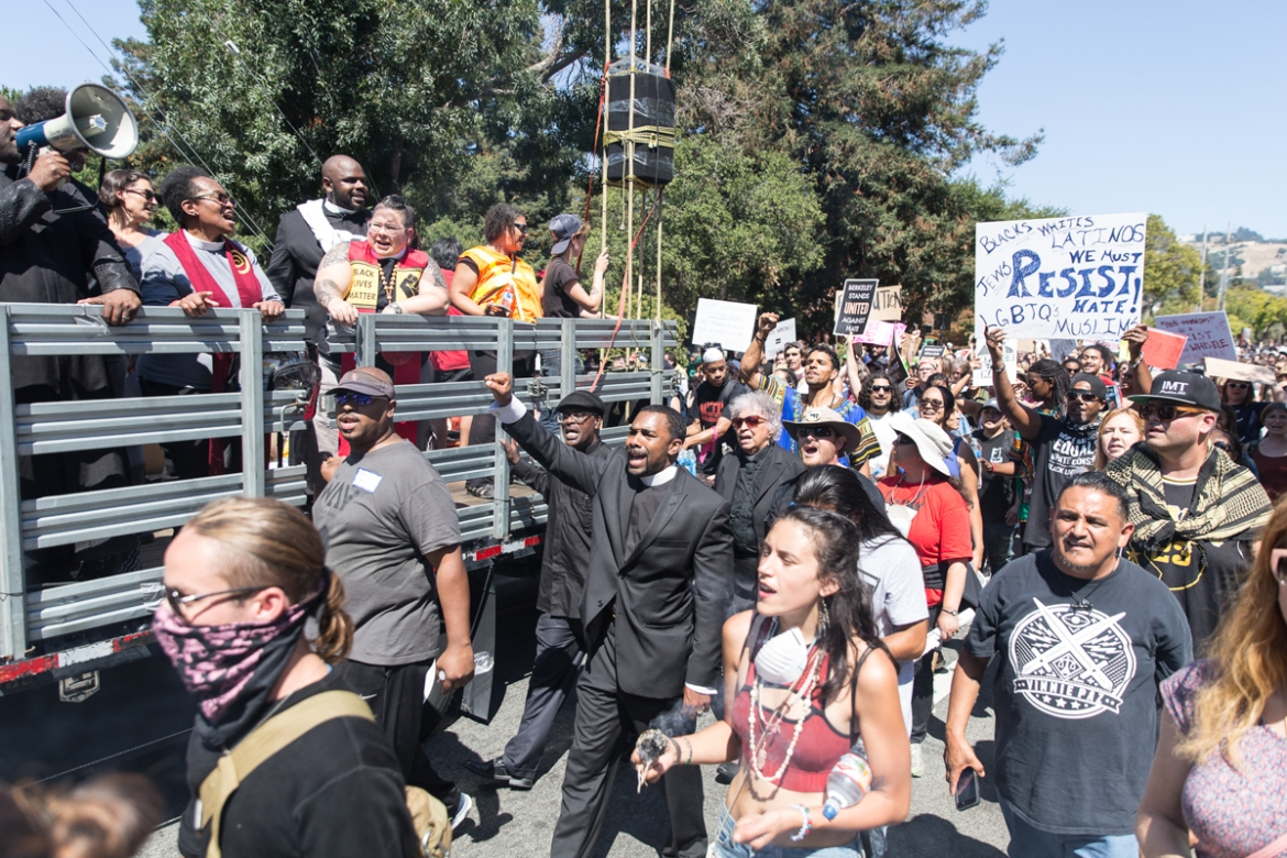 "Pastor Darnell Hammock (centre) walks down Hearst Avenue in Berkeley during a victory march following the day's action. ""We're out here to denounce white supremacy and hate. Often the church has been silent and complicit and on the wrong side of history, and I wanted people to know we stand with those who suffer under those emboldened by Trump.""' [Kelly Lynn Lunde/Al Jazeera]"