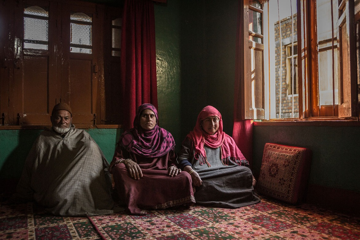 Ghullam Muhammad Mir, left, and his daughters-in-law Nasima Begum, centre, and Hasina Begum, right, pose for a portrait at their home in Tantray Pora, Delina, Baramulla district in Indian-administered Kashmir. They suspect their men were arrested and one disappeared, tortured to death or executed. [Violeta Santos Moura/Al Jazeera]