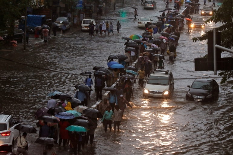 Commuters walk through water-logged roads after rains in Mumbai [Shailesh Andrade/Reuters]