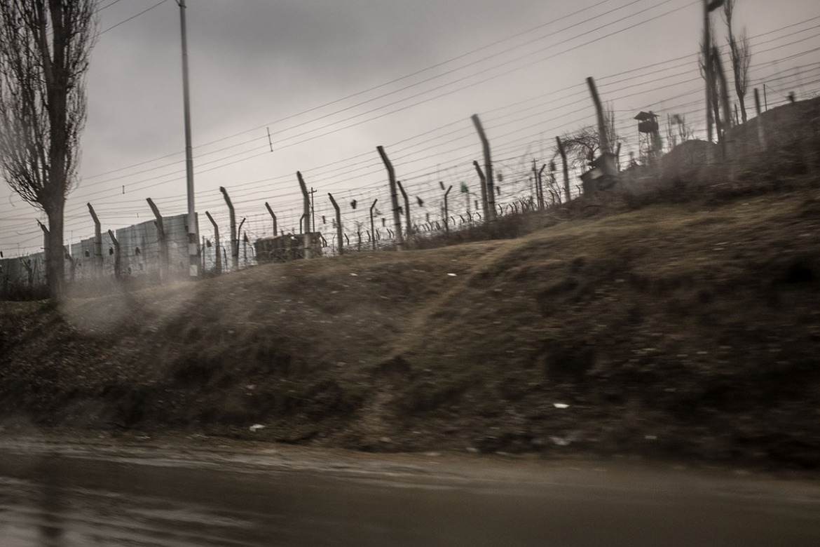 The external fence surrounding an Indian military camp sits on the main road between the Kashmiri capital of Srinagar and the border district of Baramulla. Kashmiris say they feel uncomfortable when walking past these camps because of what they suspect happens inside these military facilities. [Violeta Santos Moura/Al Jazeera]