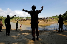 Members of Border Guard Bangladesh (BGB) command to the Rohingya people not to cross the canal, who take shelter in No Man's Land between Bangladesh-Myanmar border, in Cox's Bazar, Bangladesh [Reuters]