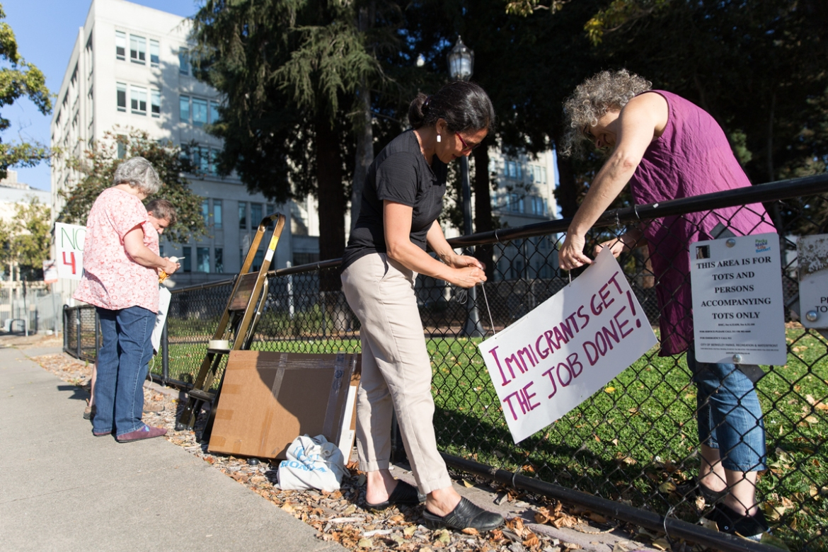 'When we heard about this event, we wanted to express the values of our community without confrontation,' says Berkeley resident Dibsy Matcha (left). She and others put up signs in anticipation of right wing activists. 'We feel passionate and frustrated and wanted to do something,' says Brigitte Yeh (centre) adjusting a sign with friend Robin Miller. [Kelly Lynn Lunde/Al Jazeera]