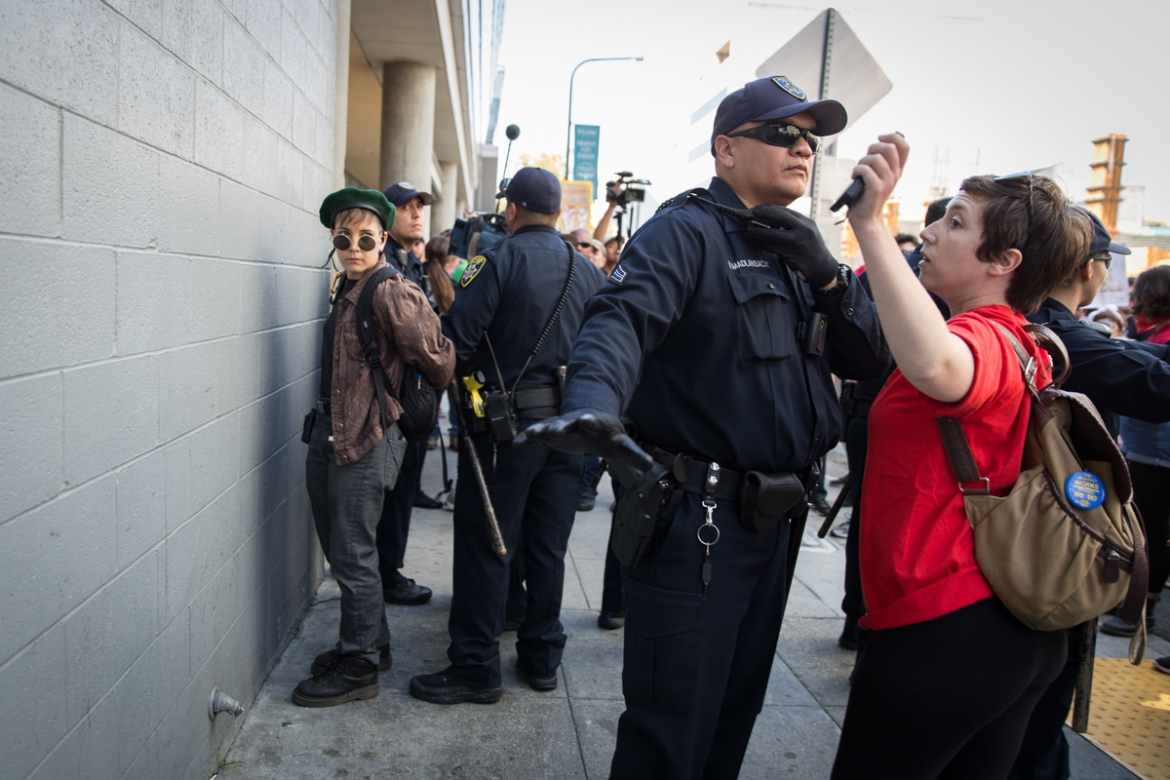 Police arrest a young protester during a march from near the University of California, Berkeley, to Martin Luther King Jr Civic Center Park on Sunday morning. Police arrested 12 people during the day, including black-clad antifa members who drove out several right-wing activists from the park. [Kelly Lynn Lunde/Al Jazeera]