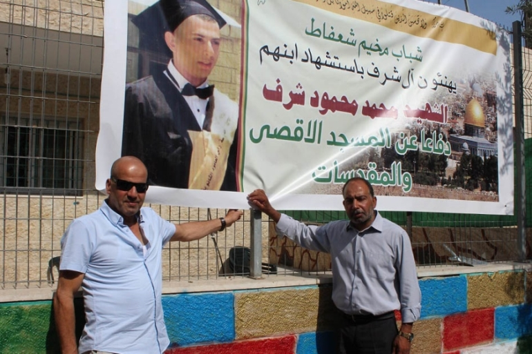 Musa Sharaf and Mahmoud Sharaf, the uncle and father of Mohammed Sharaf, stand by his poster in Wadi Qadum [Nigel Wilson/Al Jazeera]