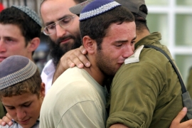 Jewish settler cries as he embraces an Israeli soldier during the evacuation of Netzarim settlement in the Gaza Strip on August 22, 2005 [Dan Balilty/Daylife]