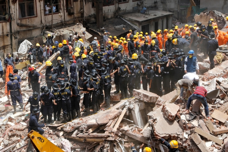 Firefighters and rescue workers search for survivors [Shailesh Andrade/Reuters]