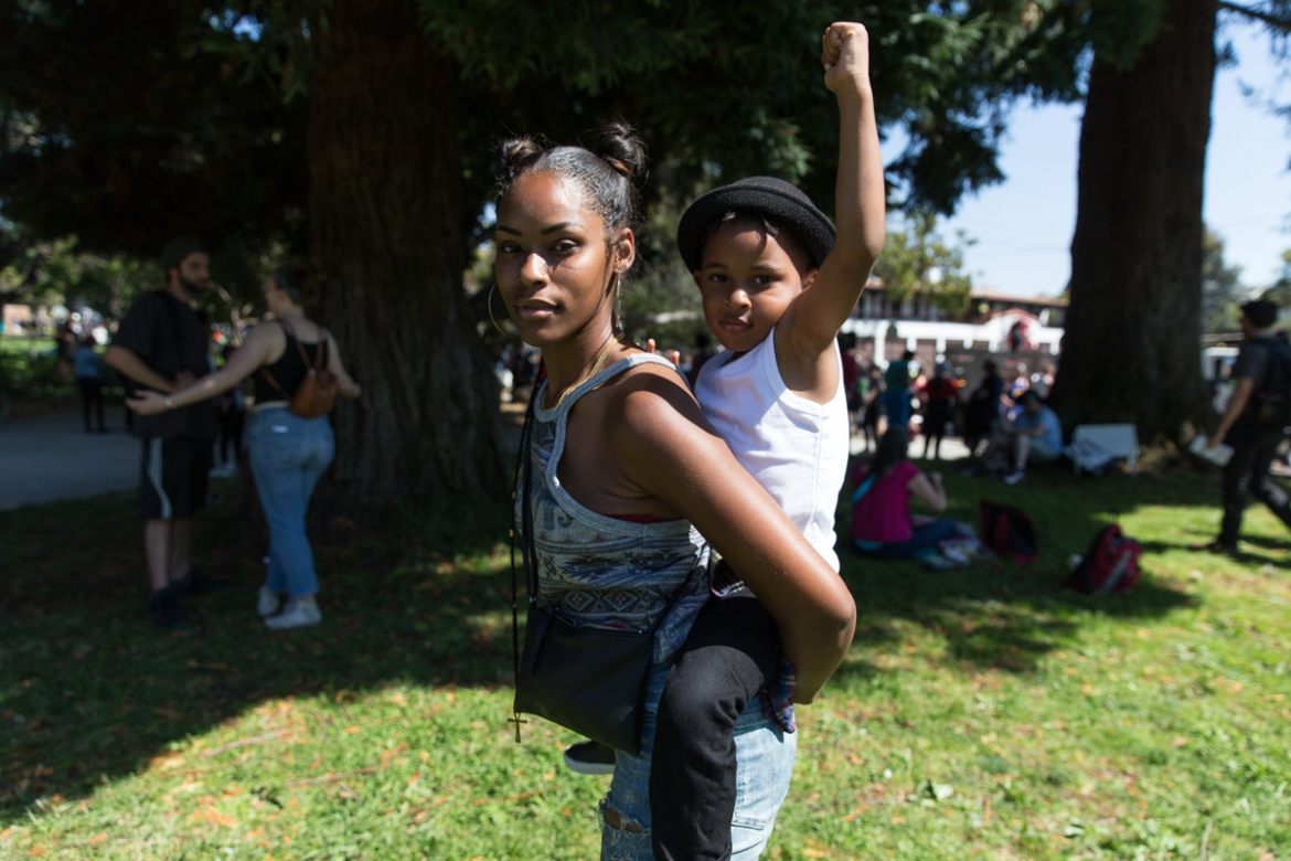 Following a final gathering at Berkeley's Ohlone Park, 26-year-old Berkeley native Tiana Lee stands with her four-year-old son True. 'I believe all people need to support each other, it's about time we stand together,' says the Black Lives Matter activist and mother. 'Today was a success. It's history.' [Kelly Lynn Lunde/Al Jazeera]