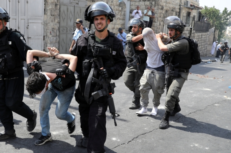 Israeli occupation forces arrest young Palestinian men outside Jerusalem's Old city on July 21, 2017 [Reuters]