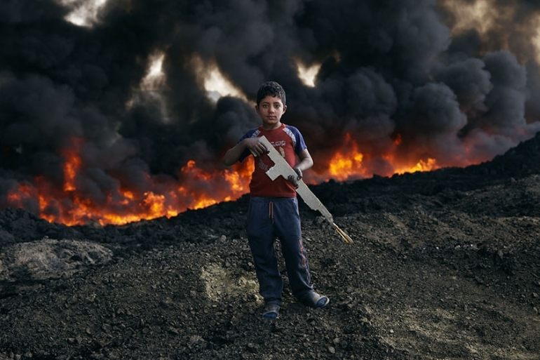 A young Iraqi boy plays near the site of one of the oil fires. Communities living around the blazes are potentially at risk for long-term health problems [Joey Lawrence/Al Jazeera]