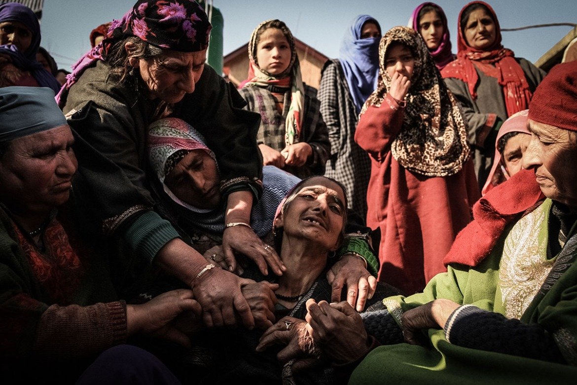 Relatives and neighbours in Panjpora village try to comfort the mother of 34-year-old Ghulam Mohi ud Din Rather in the village of Panjpora who was killed in an ambush by Kashmiri fighters. [Violeta Santos Moura/Al Jazeera]