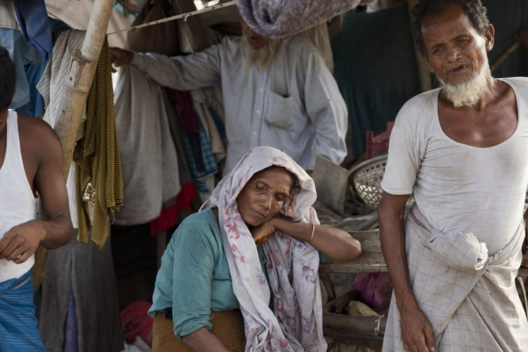 Rohingya refugees stand inside their slum on the outskirts of New Delhi, India, in a photo from 2015 [Tsering Topgyal/AP]