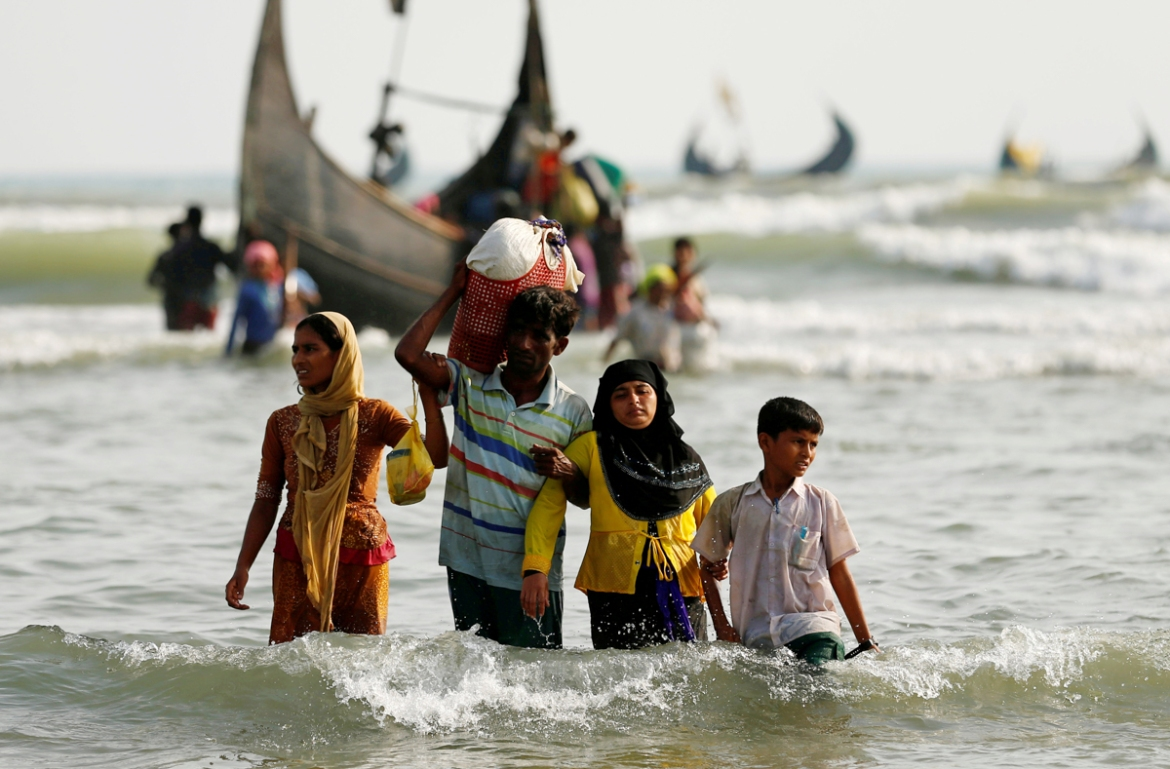 Rohingya refugees walk to the shore with their belongings after crossing the Bangladesh-Myanmar border by boat through the Bay of Bengal. [Mohammad Ponir Hossain/Reuters]