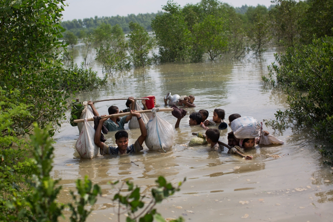 A Rohingya family reaches the Bangladesh border after crossing a creek of the Naf river on the border with Myanmar, in Cox's Bazar's Teknaf area. [Bernat Armangue/AP Photo]