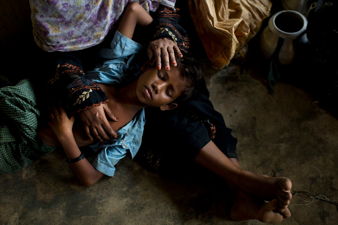 A Rohingya woman comforts her exhausted son as they take shelter inside a school after having just arrived from the Myanmar side of the border at Kutupalong refugee camp, Bangladesh. Some 164,000 Rohingya from the area have fled across the border into Bangladesh in less than two weeks since August 25. [Bernat Armangue/AP Photo]