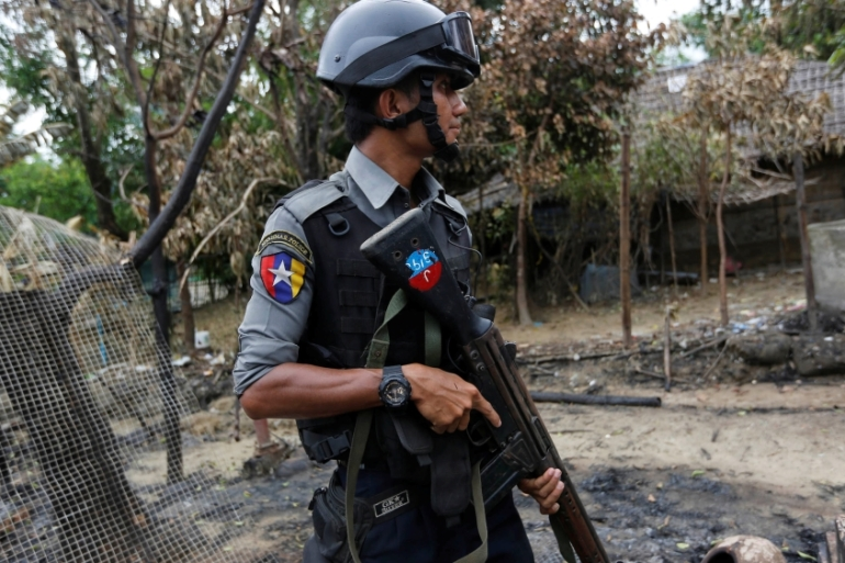 A police officer stands guard near a house that was burned down in Maungdaw, northern Rakhine state [Soe Zeya Tun/Reuters]