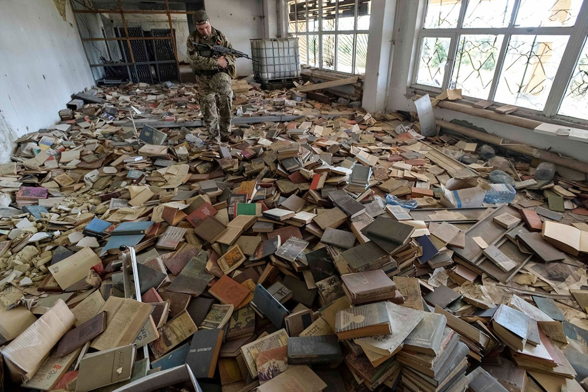 A Ukrainian serviceman inspects an abandoned library, with numerous books seen on the floor, near his position on the front line in the town of Maryinka, Ukraine. [Oleksandr Klymenko/Reuters]