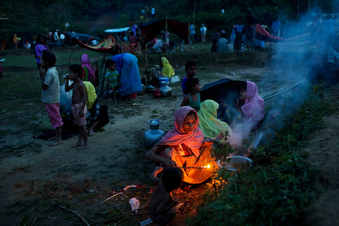 Rohingya, who have just crossed over to Bangladesh from Myanmar, cook a meal near Cox's Bazar's Gundum area. [Bernat Armangue/AP Photo]