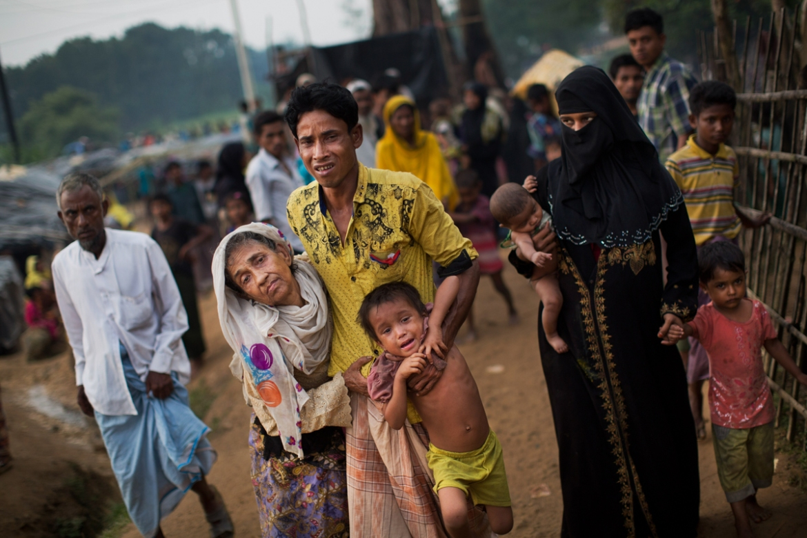 An exhausted Rohingya helps an elderly family member and a child as they arrive at Kutupalong refugee camp after crossing from Myanmar to the Bangladesh side of the border, in Ukhia. The man said he lost several family members in Myanmar. [Bernat Armangue/AP Photo]