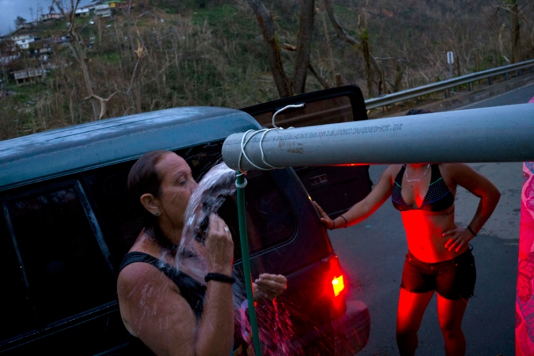 People bathe in water piped from a creek in the mountains in Naranjito, Puerto Rico [Ramon Espinosa/AP]