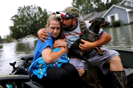David Gonzalez comforts his wife Kathy after being rescued from their home flooded by Tropical Storm Harvey in Orange, in the US state of Texas. [Jonathan Bachman/Reuters]