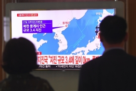 South Koreans watch a television news screen showing a map of the epicentre of an earthquake detected in North Korea on Saturday [Jung Yeon-je/AFP]