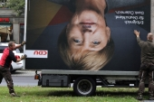 Workers remove an election campaign billboard showing German Chancellor Angela Merkel, the day after the general election in Berlin, Germany on September 25, 2017 [Christian Mang/Reuters]