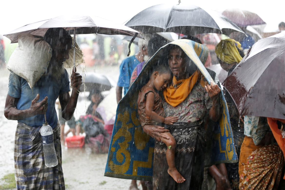 Rohingya refugees stand in an open place during heavy rain, as they are held by Border Guard Bangladesh after illegally crossing the border, in Teknaf, Bangladesh. [Mohammad Ponir Hossain/Reuters]