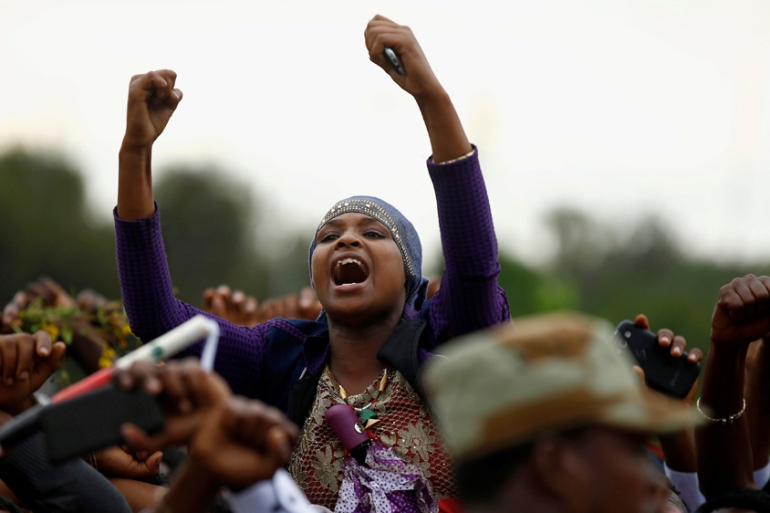 Demonstrators chant slogans while flashing the Oromo protest gesture during Irreecha in 2016 [Tiksa Negeri/Reuters]