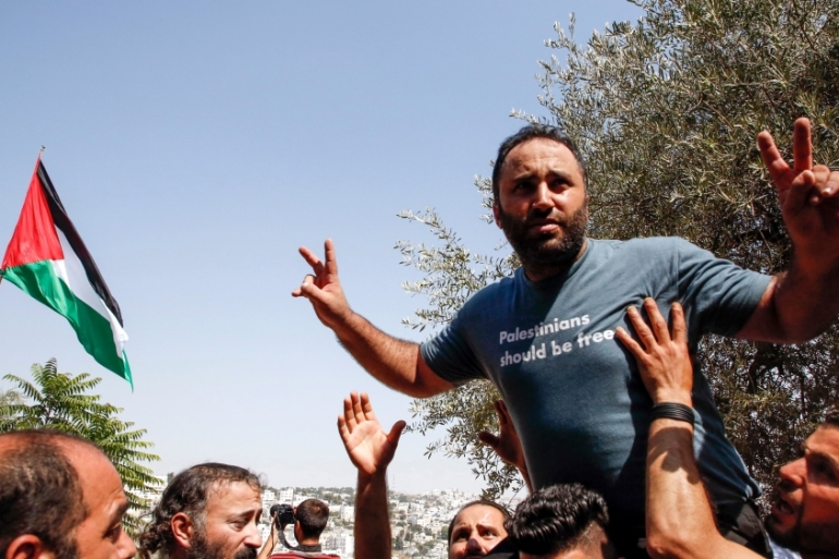 Issa Amro is welcomed by supporters after being released on bail by a Palestinian court [Hazem Bader/AFP/Getty Images]