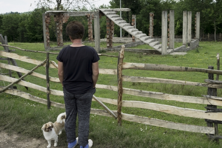 A survivor looking at a destroyed family home in Eastern Bosnia. State assistance and aid programmes often don't reach women in remote areas [Ziyah Gafic/ Amnesty]