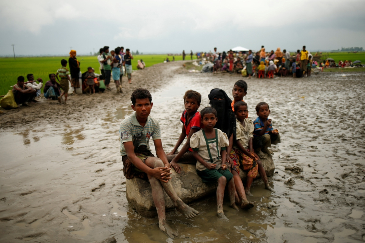 Rohingya refugees sit as they are temporarily held by the Border Guard Bangladesh in an open area after crossing the border. [Mohammad Ponir Hossain/Reuters]