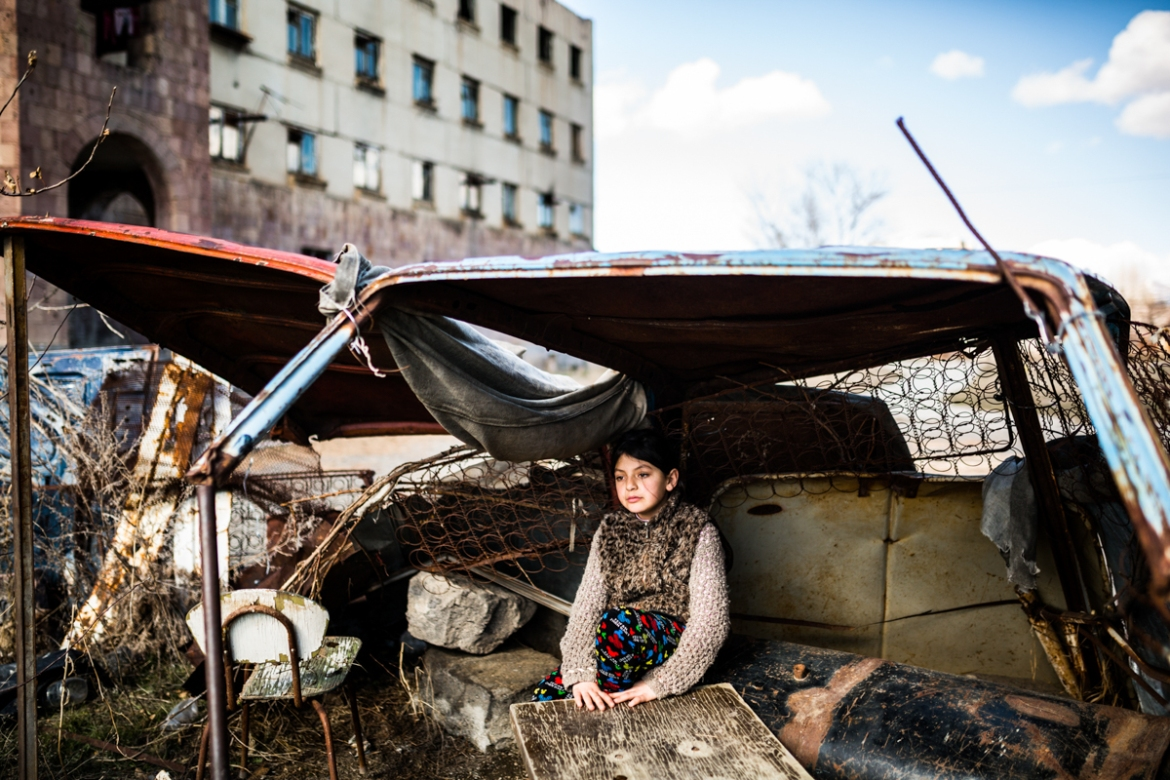 Syuzanna, aged 9, plays inside old rusty cars in front of the abandoned building where she lives with her family. Ten days ago, Syuzanna's father committed suicide because of debts he was unable to repay. [Yulia Grigoryants/Al Jazeera]