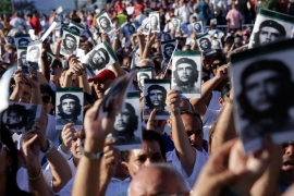 Cubans wave photos of Che Guevara to celebrate the 50th anniversary of his death in Santa Clara, Cuba. [Sven Creutzmann/Mambo photo/Getty Images]