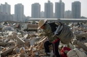A migrant worker carries scrap material she collected from debris of demolished buildings at the outskirts of Beijing, China [Thomas Peter/Reuters]