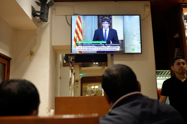 Customers at a bar in Catalonia's Vic watch Puigdemont's televised address [Vincent West/Reuters]