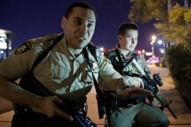 Police officers advise people to take cover near the scene of the shooting near the Mandalay Bay Resort and Casino [John Locher/AP]