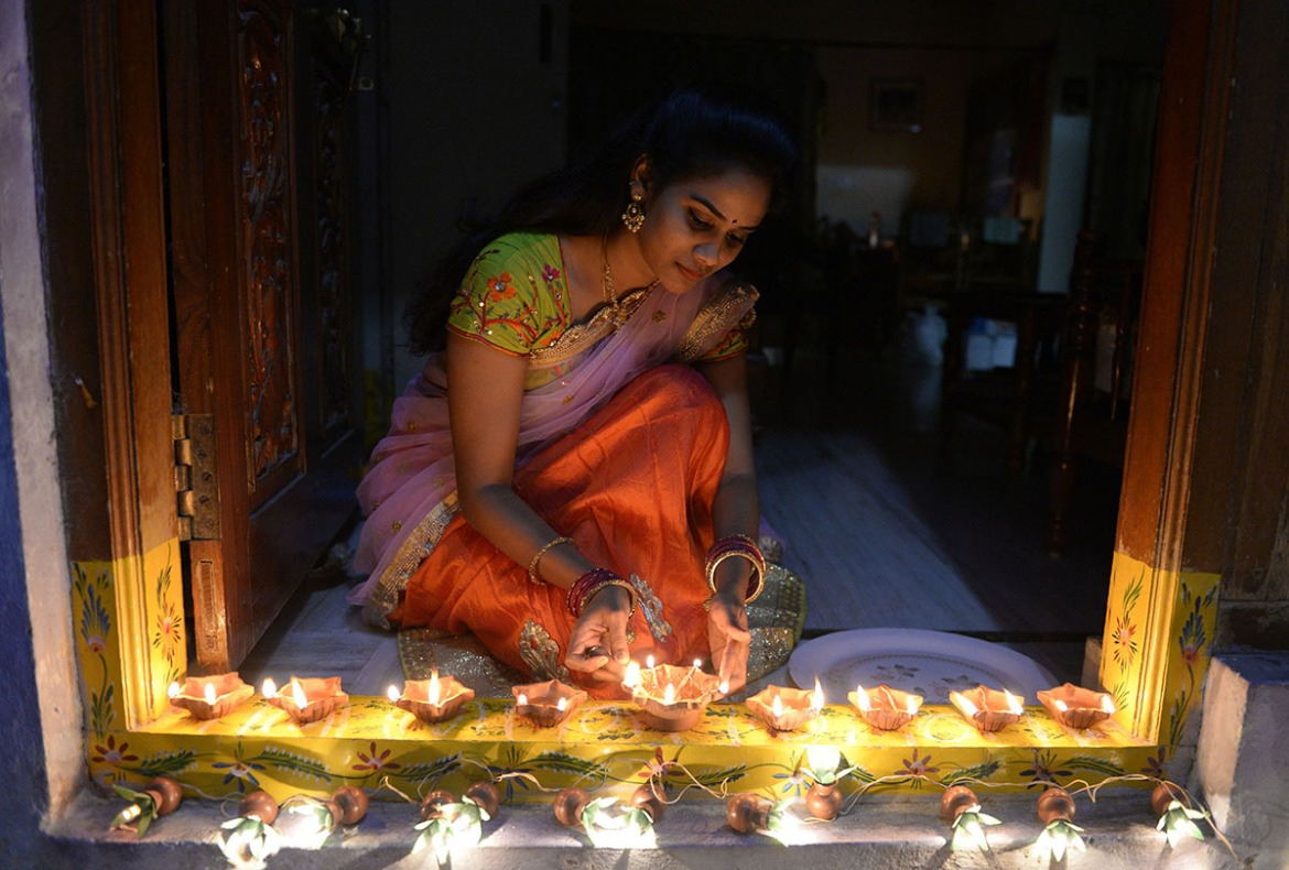 Nikitha places small 'diyas' at the entrance of her home on the eve of the Diwali festival in Hyderabad, India. [Noah Seelam/AFP/Getty Images]