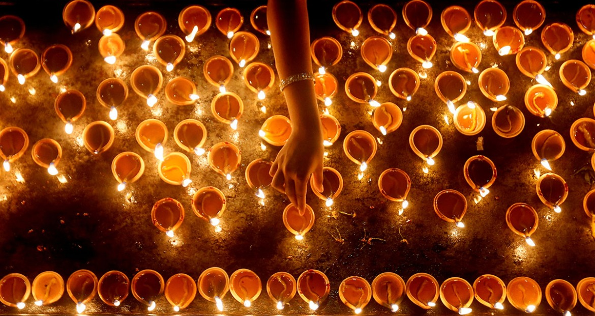 A devotee lights oil lamps at a religious ceremony during the Diwali festival at a Hindu temple in Colombo, Sri Lanka. [Dinuka Liyanawatte/Reuters]