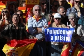 Pro-unity demonstrators with banners calling for the imprisonment of Catalan President Carles Puigdemont, gather in Madrid, Spain [Susana Vera/Reuters]