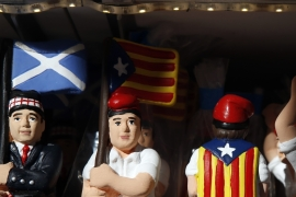 Clay 'caganers' wearing Catalan separatist flags and Scottish flags are sold at the Santa Llucia Christmas market in central Barcelona [Reuters]