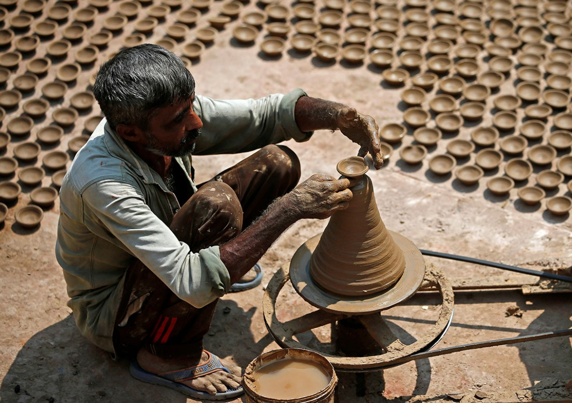 A man makes earthen lamps which are used to decorate temples and homes during the Hindu festival of Diwali, at a workshop in Ahmedabad, India. [Amit Dave/Reuters]