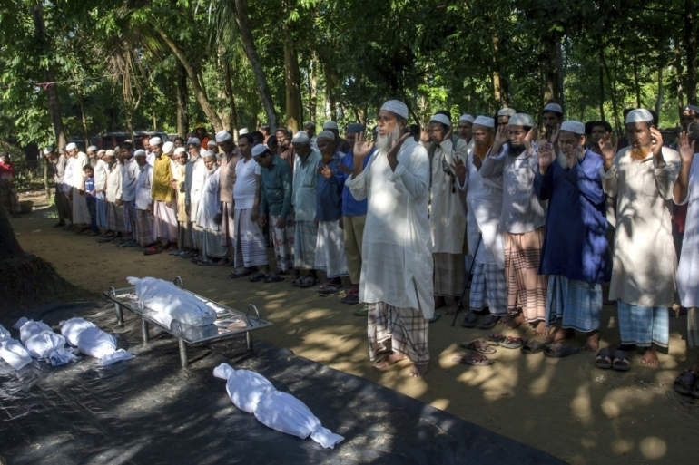 Bangladeshi villagers pray by the bodies of Rohingya Muslim children who drowned while crossing over from Myanmar into Bangladesh [Dar Yasin/AP Photo]
